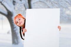 Le det lilla ung flickabarnet i vinterkläder klå upp laget och hatten som rymmer ett vitt bräde för tomt affischtavlabaner Royaltyfri Bild