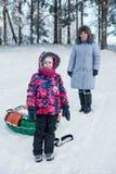 Le det lyckliga barnet med den mogna modern medan rör i vinterskog Royaltyfria Bilder