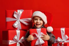 Le det roliga barnet i gåva för jul för röd hatt för jultomten hållande i hand Julfilial och klockor royaltyfria bilder
