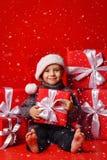 Le det roliga barnet i gåva för jul för röd hatt för jultomten hållande i hand Julfilial och klockor arkivbild