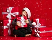 Le det roliga barnet i gåva för jul för röd hatt för jultomten hållande i hand Julfilial och klockor arkivfoto