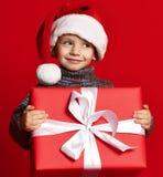 Le det roliga barnet i gåva för jul för röd hatt för jultomten hållande i hand Julfilial och klockor royaltyfri foto