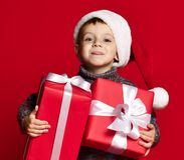 Le det roliga barnet i gåva för jul för röd hatt för jultomten hållande i hand Julfilial och klockor royaltyfri fotografi