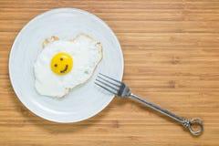 Le det stekte ägget som ligger på en träskärbräda med morgoninskriften nära den Klassiskt frukostbegrepp arkivfoton