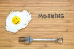 Le det stekte ägget som ligger på en träskärbräda med morgoninskriften nära den Klassiskt frukostbegrepp Royaltyfri Bild