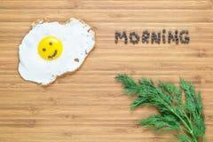 Le det stekte ägget som ligger på en vit platta på en träskärbräda med gruppen av dill och morgoninskriften nära den fotografering för bildbyråer
