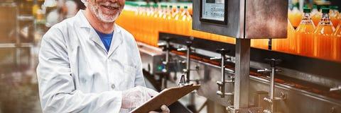 Le det underhållande rekordet för fabrikstekniker på skrivplattan i fabrik royaltyfria foton