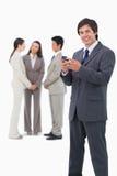 Le detaljhandlare med mobiltelefon och kollegor Arkivbild