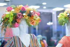 Le devanture de magasin avec des mannequins a décoré les fleurs décoratives image stock