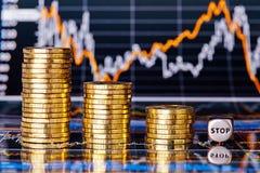 Le diagramme financier de tendance à la baisse, piles de pièces de monnaie d'or et découpe le cube Image stock