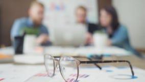 Le diagramme financier sous des verres et les collègues d'affaires ont la réunion à l'arrière-plan clips vidéos