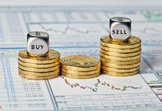 Le diagramme, les pièces de monnaie et les cubes financiers en matrices avec les mots vendent l'achat. Image libre de droits