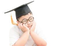 Le diplômé asiatique d'enfant d'école était ennuyeux avec le chapeau d'obtention du diplôme d'isolement Image libre de droits