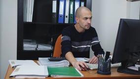 Le directeur au bureau prépare le rapport financier pour la gestion Travaillant avec des documents, dactylographiant sur l'ordina banque de vidéos