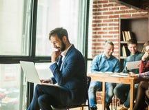 Le directeur avec un ordinateur portable et des affaires team dans un lieu de travail dans un MOIS Photo stock