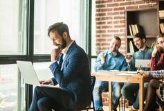 Le directeur avec un ordinateur portable et des affaires team dans un lieu de travail dans un MOIS Image libre de droits