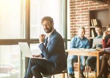 Le directeur avec un ordinateur portable et des affaires team dans un lieu de travail dans un MOIS Photographie stock libre de droits