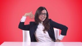 Le directeur de la jeune fille s'asseyant dans son bureau et a plaisir à onduler une transaction réussie Fond rouge banque de vidéos