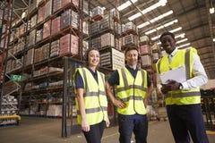 Le directeur et les collègues d'entrepôt de distribution regardent à l'appareil-photo photographie stock