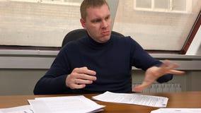 Le directeur pousse les feuilles de documents et de jets sur le bureau dans le bureau clips vidéos