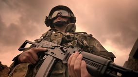 Le dirigeant puissant dans le camouflage se tient sur le fond de cieux nuageux, tenant l'arme à feu automatique, illustration de  clips vidéos