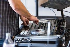Le disc-jockey utilise les contrôles sains à l'événement photographie stock