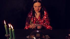 Le diseur de bonne aventure gitan à la table par lueur d'une bougie écarte des cartes de fortunetelling banque de vidéos