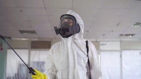 Le Disinfector dans des vêtements spéciaux et un masque protecteur pulvérise le pesticide banque de vidéos