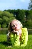 Le disposizioni della ragazza su un'erba Immagini Stock
