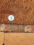 Le disque compact était cassé sur les grilles brunes de drain de sol et de ciment avec le fond abstrait photo stock