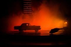 Le disque vinyle de vintage jouant sur le joueur et la guitare acoustique sur le fond avec l'orange du feu fument Concept de bleu Image stock