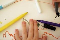 Le dita del bambino attingono la carta con le penne di colore fotografia stock