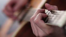 Le dita dell'uomo che giocano sui cerchi della chitarra video d archivio