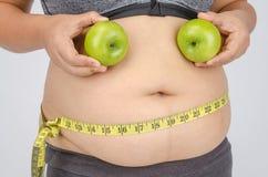 Le dita della donna che misurano il suo grasso della pancia Immagini Stock Libere da Diritti