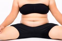 Le dita della donna che misurano il suo grasso della pancia Immagine Stock