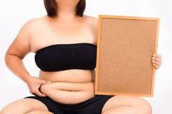 Le dita della donna che misurano il suo grasso della pancia Fotografie Stock