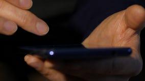 Le dita della donna su uno schermo attivabile al tatto dello smartphone Internet di lettura rapida della ragazza per acquisto onl archivi video
