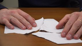 Le dita piegano un foglio di carta dai residui lacerati stock footage