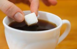 Le dita tengono un pezzo dello zucchero di grumo sopra la tazza di tè immagine stock