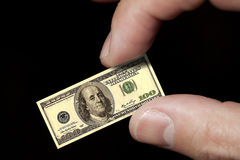 Le dita tengono una piccola nota del dollaro Fotografie Stock Libere da Diritti