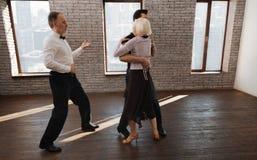 Le divan compétent de danse enseignant les personnes âgées valsent dans la salle de bal Image stock