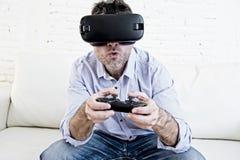 Le divan de sofa de salon d'homme à la maison excité utilisant les lunettes 3d jouent Photographie stock libre de droits