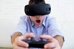 Le divan de sofa de salon d'homme à la maison excité utilisant les lunettes 3d jouent Photo libre de droits