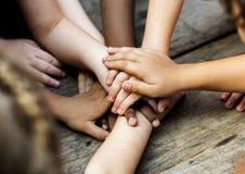 Le diverse mani sono si uniscono sulla tavola di legno Immagini Stock