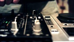 Le DJ à une cabine de console tournant et affaiblisseurs et boutons émouvants de mélangeur clips vidéos