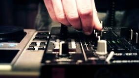 Le DJ à une cabine de console tournant et affaiblisseurs et boutons émouvants de mélangeur banque de vidéos