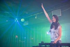 Le DJ assez féminin ayant l'amusement tout en jouant la musique Photos stock