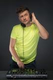 Le DJ au travail d'isolement sur le fond gris-foncé Images libres de droits