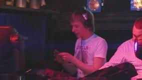Le DJ dans des écouteurs dansent à la plaque tournante avec le disque dans des mains sur la partie dans la boîte de nuit divertis banque de vidéos