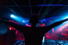 Le DJ dans des écouteurs ondulant ses bras à la silhouette de boîte de nuit de partie avec la lumière colorée Images stock